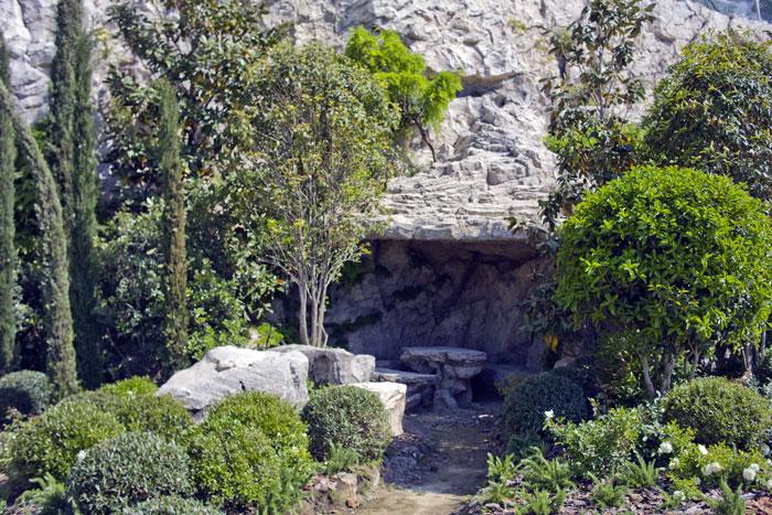 Особенности строительства из арт-бетона позволяют делать в подпорных стенах пещеры с каменной мебелью.