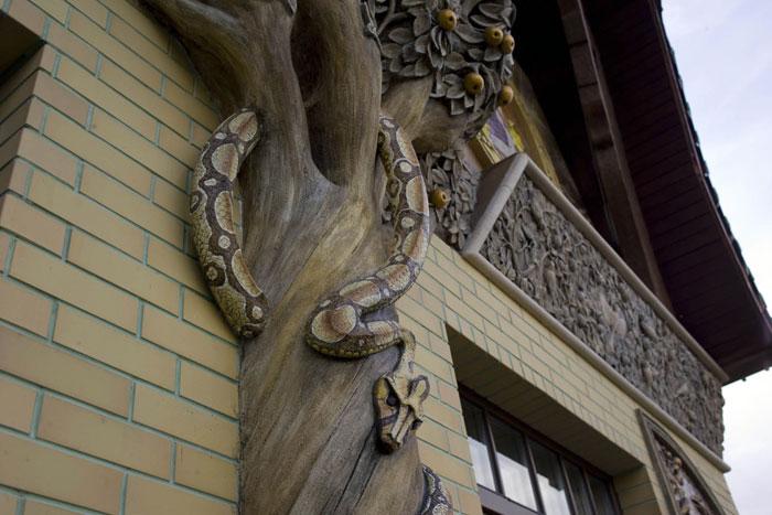 Скульптура змеи и дерева из арт-бетона на фасаде здания.