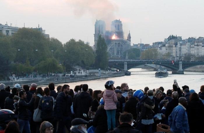 Парижане и туристы с ужасом наблюдают за происходящим. | Фото: REUTERS.