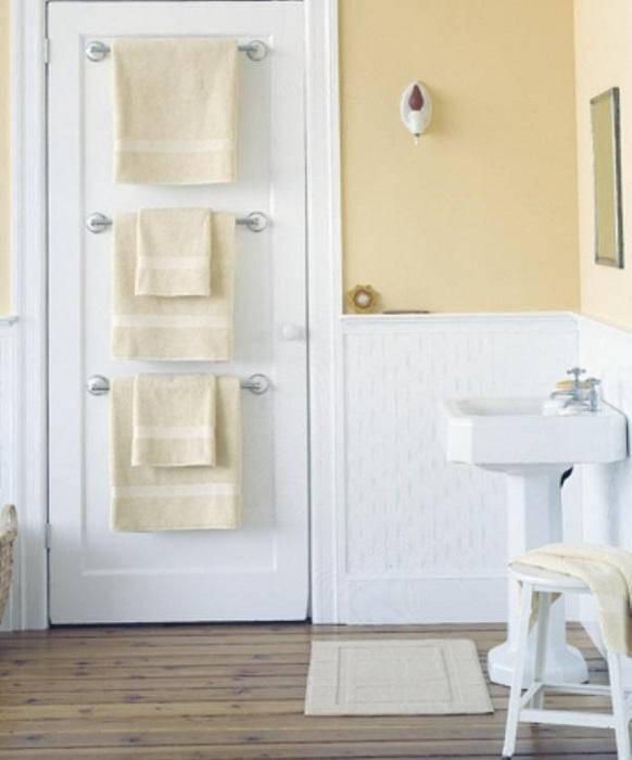 Полотенца можно хранить на вешалках, прикрепленных к двери