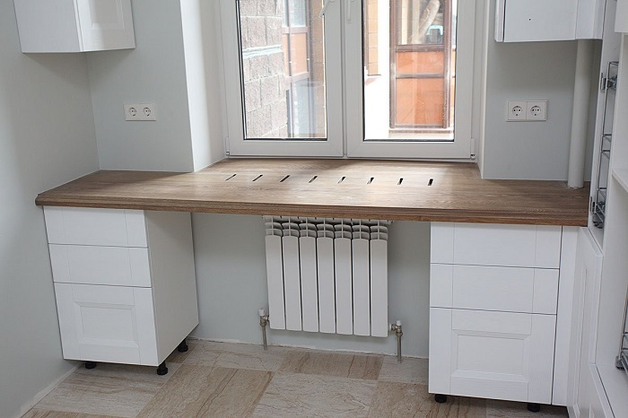 Если батарея располагается под подоконником, то над ней можно сделать стол. / Фото: roomester.ru