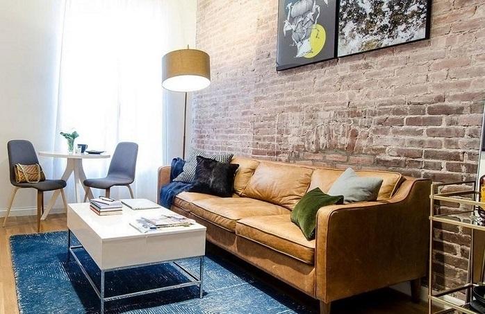Кожаный диван отлично комбинируется с кирпичной стеной