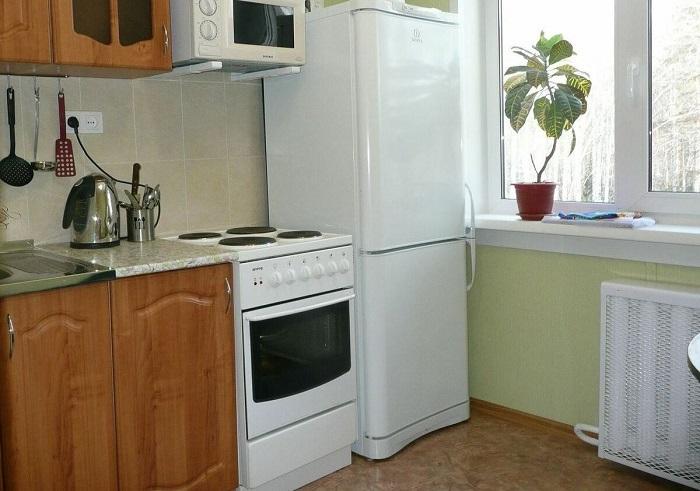 Плита нагревает стенки холодильника и не дает ему нормально работать. / Фото: Stroy-podskazka.ru