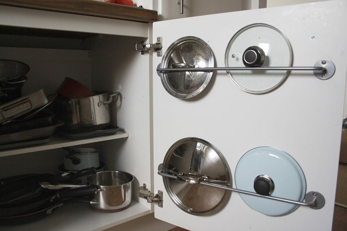 Закрепите на дверце шкафа перекладину для крышек. / Фото: Zen.yandex.ua