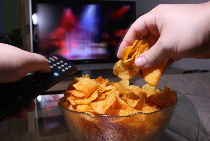 Смотря телевизор, мы не контролируем количество съеденного. / Фото: golos.ua