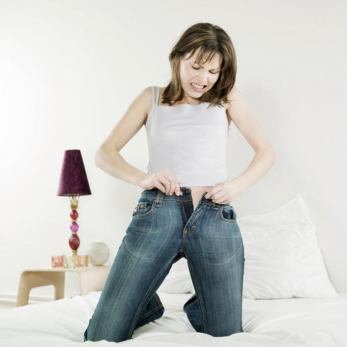 Девушка втягивает живот, чтобы застегнуть джинсы. / Фото: wikihow.com
