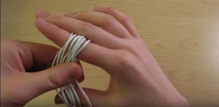 Другой рукой аккуратно возьмите «восьмёрку» ровно по центру и снимите с пальцев