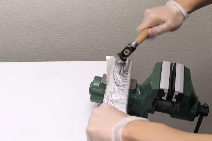 Японец молотком ровняет рулон фольги.