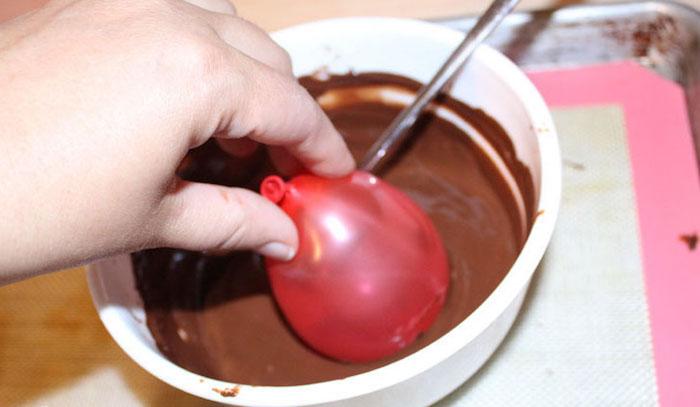 Погрузите шарик  в шоколад до половины.