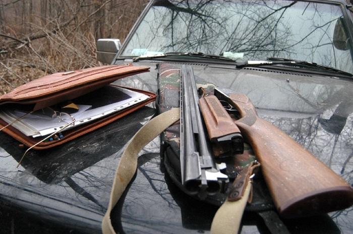 Огнестрельное оружие на капоте автомобиля.