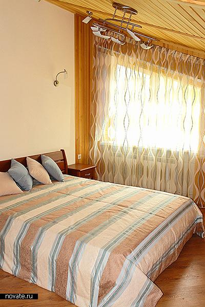Совершенно нейтральный интерьер спальни преобразился, когда в нем появилось полосатое покрывало и штора в этом же стиле. © Артис