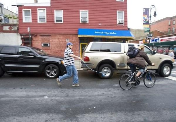 Участник массового нью-йоркского флешмоба инсценирует погоню невидимой собаки за велосипедом