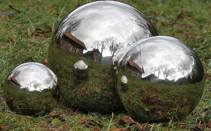 Предметы с зеркальной поверхностью на газоне