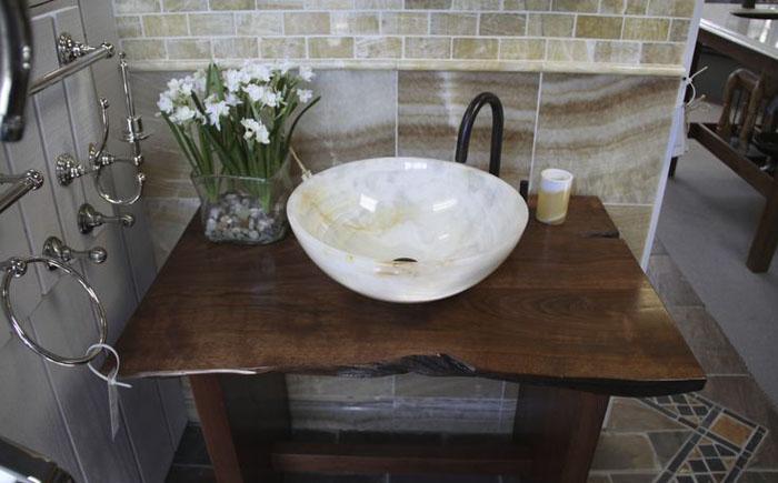 Мраморная раковина с бронзовым смесителем на деревянной столешнице