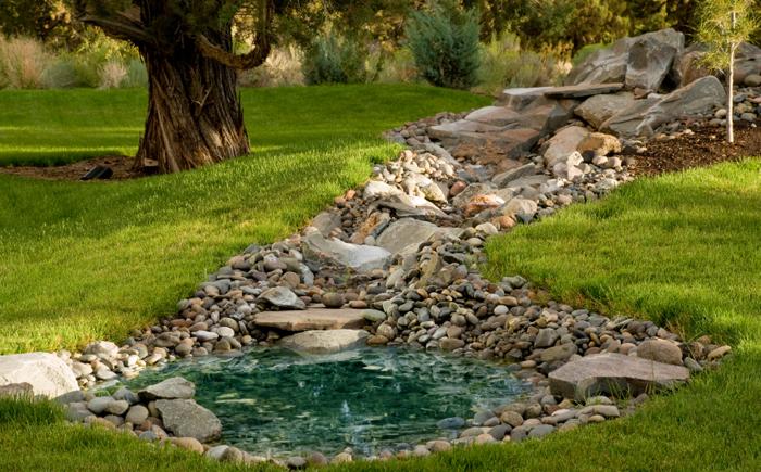 Маленький пруд с  небольшим фонтаном. Густая трава и различные фигурки украшают каменные берега водоёма.