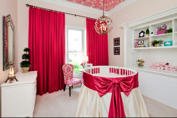 Комната с круглой кроваткой в белых тонах с красным акцентом
