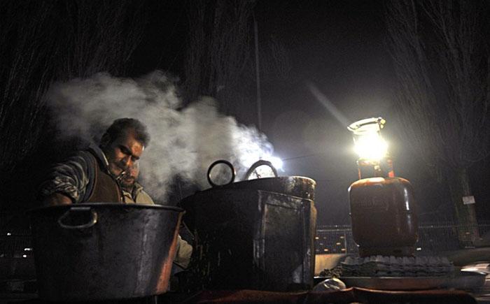 Кашмирский продавец готовит закуски на улице Сринагара.