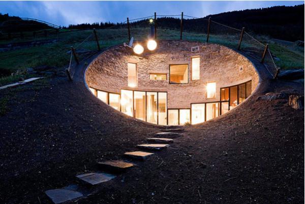 Подземный дом эллиптической формы с видом на Альпы