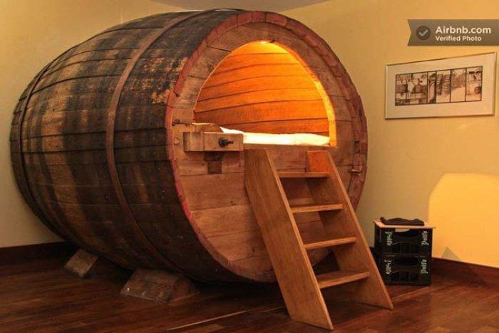 Кровать внутри деревянной пивной бочки.