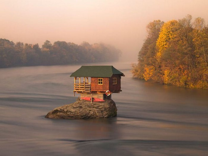 Домик, балансирующий на камне посреди озера.