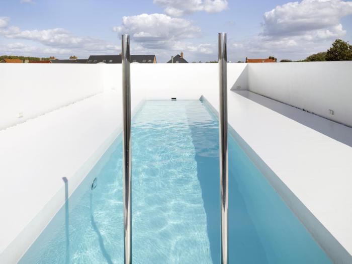 Белоснежный бассейн в стиле минимализм в окружении старинных построек.