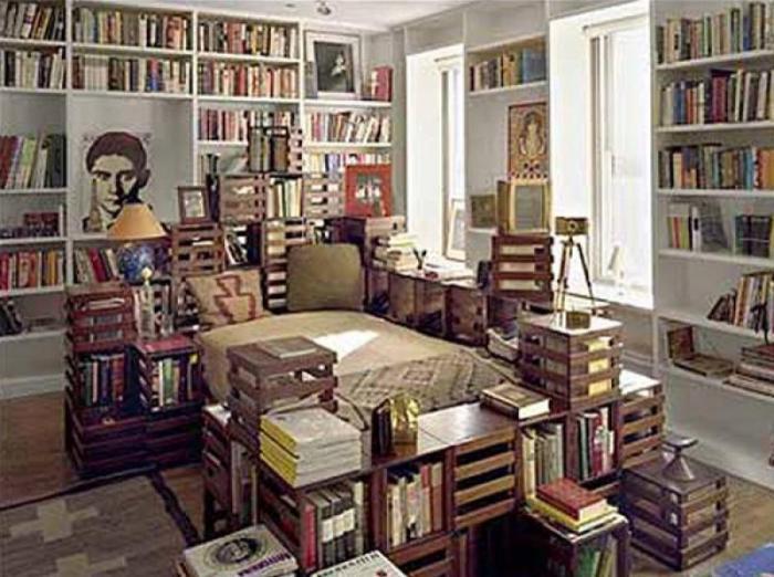 Кровать, окруженная книжными полками.