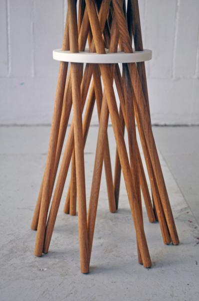 Прутья древесины, выполняющие функцию ножек стола, фиксируются круглым диском.