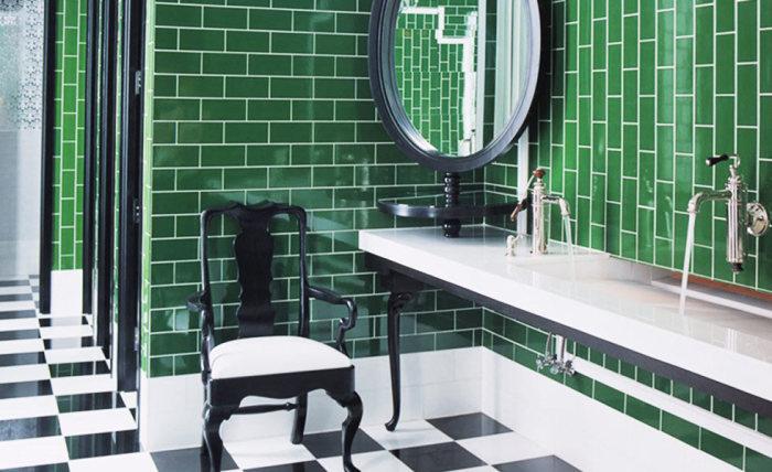 Современная ванная комната с зеленными кафельными стенами.
