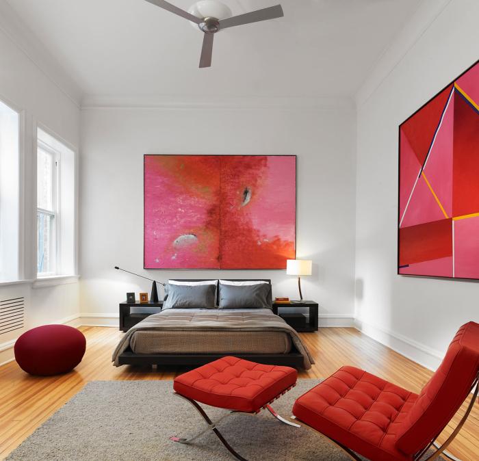 Интерьер просторной спальни с элементами красного оттенка.