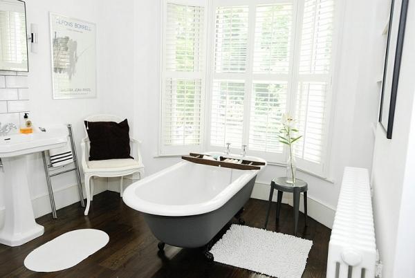 Светлая комната со стильной черной ванной.