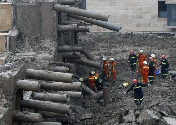 Рабочие возле рухнувшего дома.
