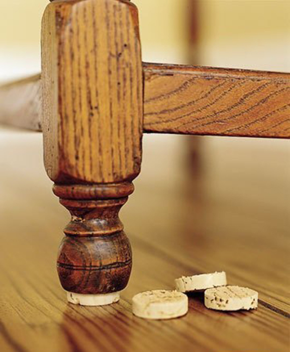 Приклейте кружки из пробки на ножки мебели, чтобы на не царапала пол. | Фото: pinterest.com.