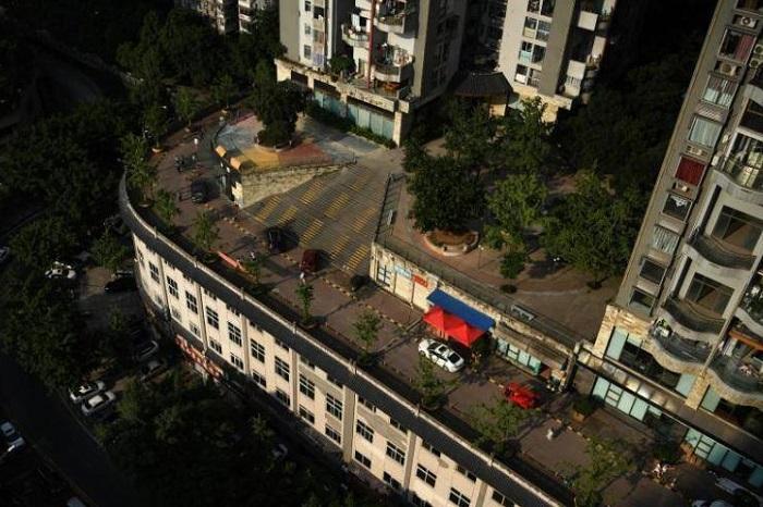 На верхнем этаже необычного дома в Чунцине есть стоянка для машин и даже нанесена дорожная разметка. | Фото: facebook.com.