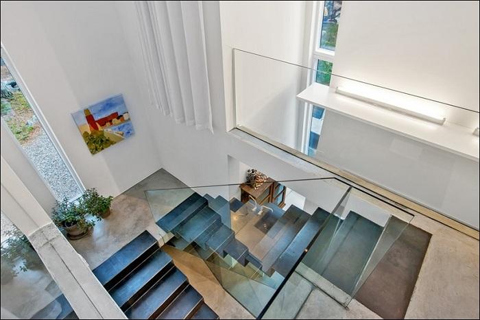 Темные железные лестницы контрастируют со светлым интерьером.
