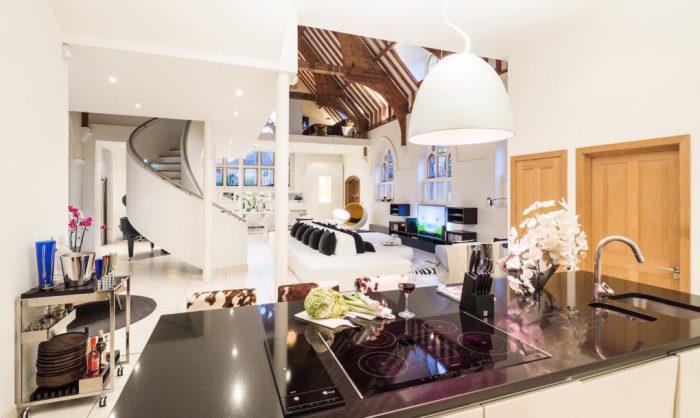 Кухня с огромной рабочей поверхностью и зеркалом на пол-стены.