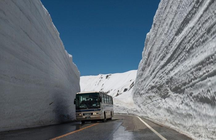 Дорога с 20-метровыми снежными сугробами на обочине.