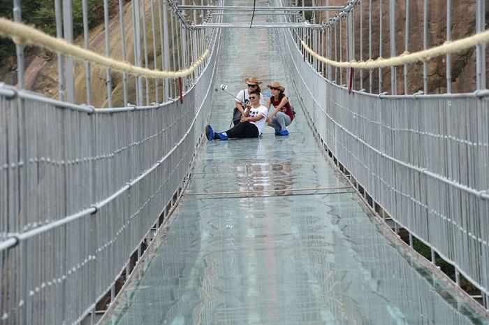Туристы делают селфи на фоне стеклянного моста.