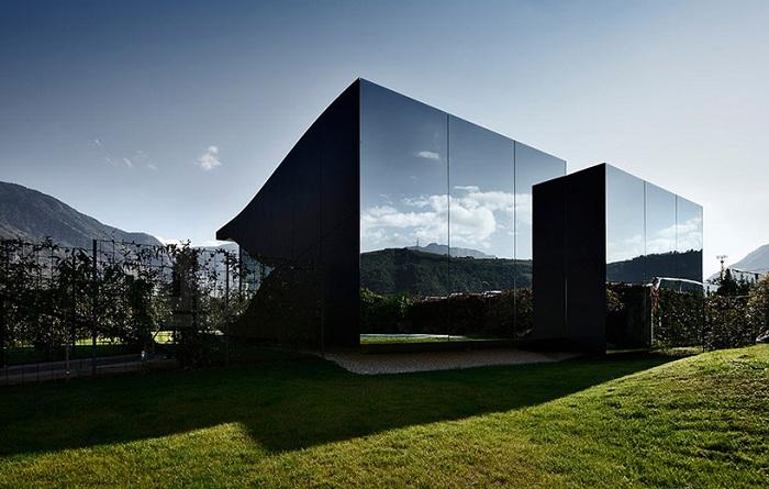 Дом с фасадом из черного алюминия, отражающим горные вершины Альп.
