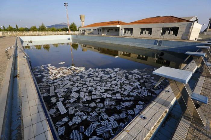 Заброшенный бассейн с отколовшейся и плавающей в нем плиткой.