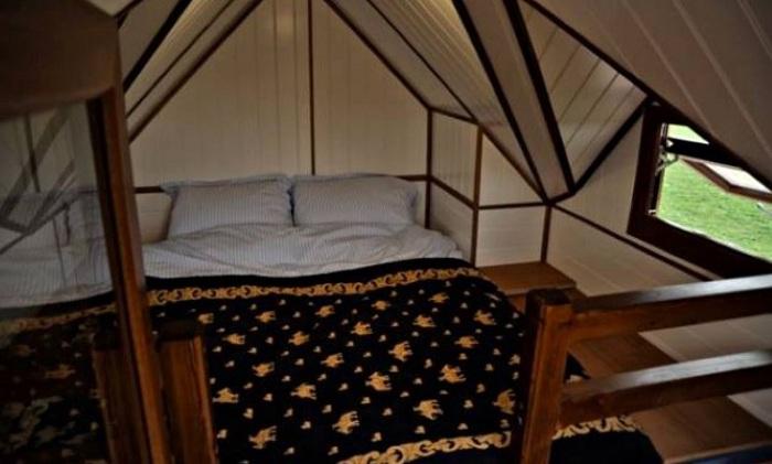 Большая кровать, установленная в крошечном домике.