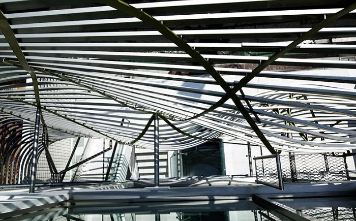 Изогнутые стальные тросы, образующие волнообразный фасад офиса.