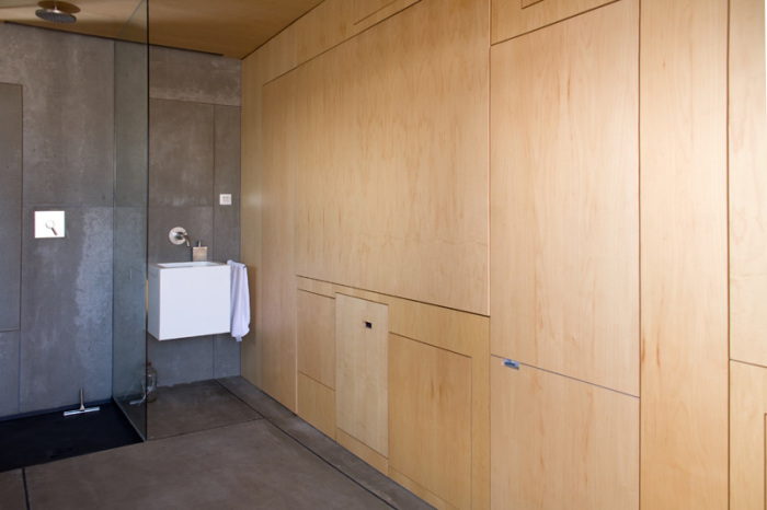Одна из стен сделана из дерева и представляет собой уникальный многофункциональный шкаф.