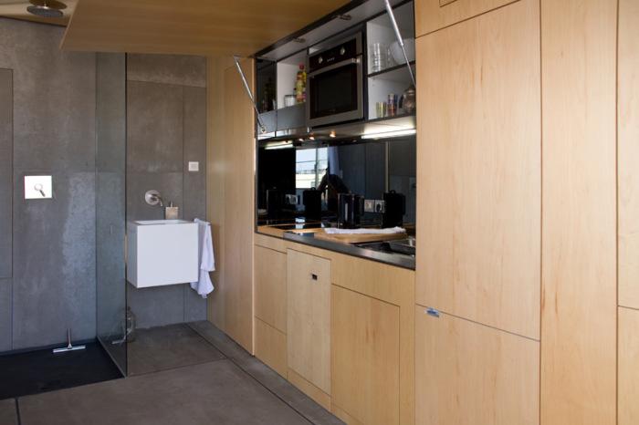 В левую часть стены встроена полноценная кухня и холодильник.