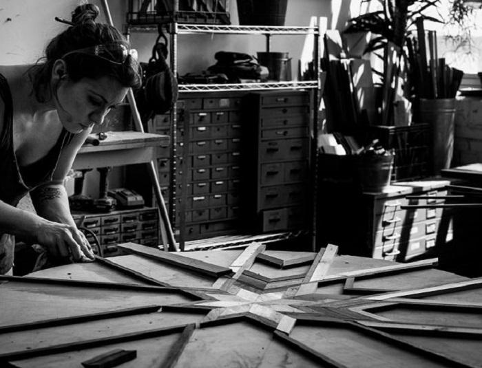 Девушка делает мозаичные столешницы из старых досок.