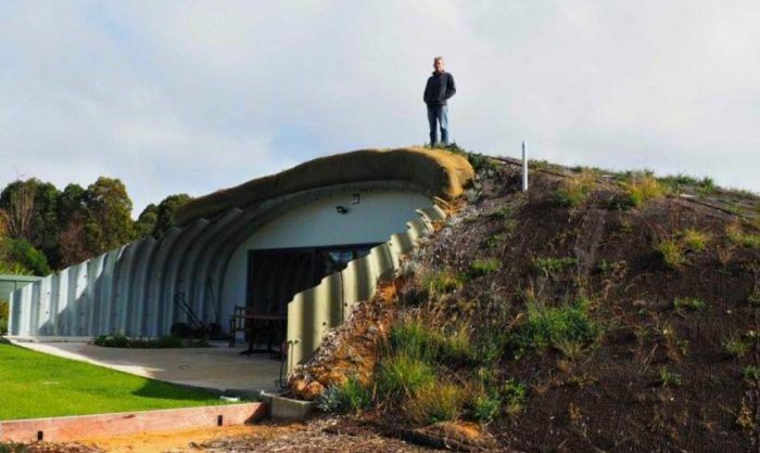 Мужчина построил дом с земляной насыпью.
