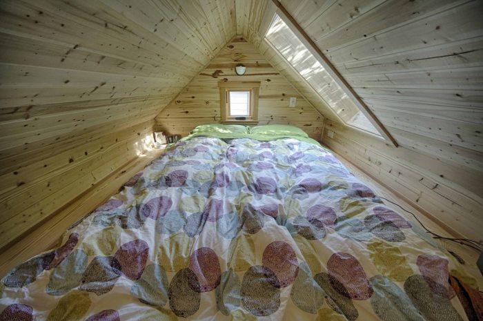 Двуспальная кровать под самой крышей.