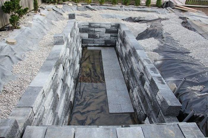 Бассейн обложили декоративным камнем.