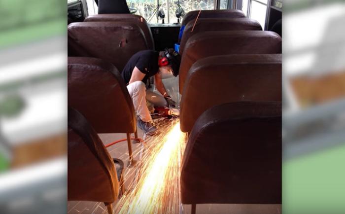 Брайн Салливан демонтирует старые сиденья в автобусе.