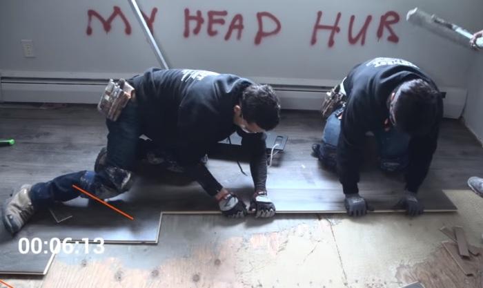 Рабочие укладывают ламинат.
