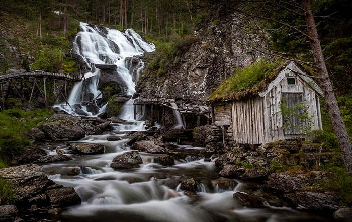 Домик с зеленой крышей у водопада Kvednafossen.